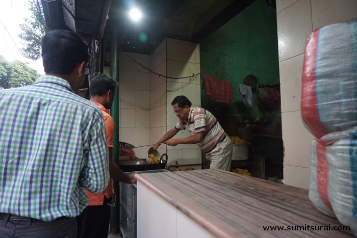 The owner frying the items while people wait eagerly
